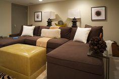 A large, brown sectional provides comfort and seating for a crowd in this neutral living area. A leather ottoman adds a hint of color, while a small end table cozies up to the sofa.