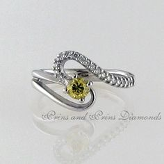 The centre stone is a 0.25ct brownish yellow round cut diamond with 0.14ct round cut white diamond pavé set on one of the curved split bands in 18k white gold