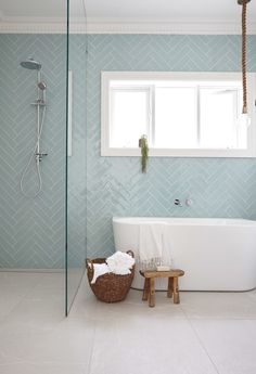 Bathroom with baby blue herringbone tiling on walls and white tub