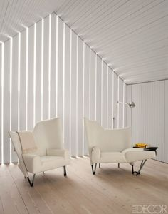 Chairs designed by Paolo Deganello and a Tolomeo floor lamp in the master bedroom; slatted planks let in sunlight.