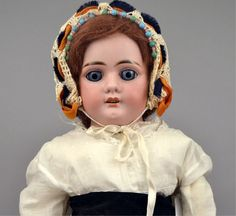 """Stephenson's Auction Antique Bisque Doll lot 81 L.H.B. German bisque shoulder head doll, kid riveted body, bisque lower arms and hands, blue glass stationary eyes, painted upper and lower lashes, painted eyebrows, open mouth with four upper teeth, accented lips, old mohair wig, wearing antique, vintage and contemporary clothes, faint blue mark on front torso (crown?), marked on head """"L.H.B. 7, Made in Germany"""", 25"""" tall, with provenance"""