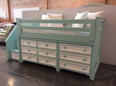 Junior stair loft with build in dressers in aqua blue with white drawers.
