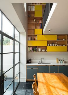 Pop of yellow cabinets makes a statement in this modern kitchen, featuring glass framed doors, eclectic cabinets, a long wooden table and matching chairs | MW Architects