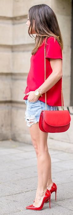 Spring / Summer - street chic style - party style - red short sleeve loose blouse + light denim distressed shorts + red stilettos + red messenger bag