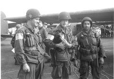 US paratroopers (who could be with the 101st if you go on the one guy's helmet marker) with a German Shepard puppy, sometime before Market-Garden