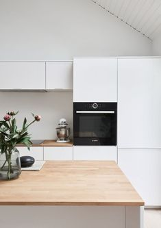 Henning Larsen Architects kitchen design. White fronts with metal band and oak countertop. It's an IKEA hack.
