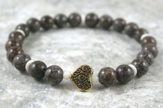 Brown snowflake jasper stacking stretch bracelet with an antiqued gold plated heart scroll focal bead, white shell beads, and bone spacers by Earthwear Collection