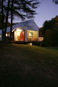 The new home's porches glow like lanterns at night. Image courtesy Chad Everhart Architect.