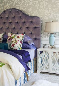 Comfy Luxury: The plush, tufted purple headboard adds comfy luxury to this bedroom. The layered, colorful bedding is an example of how you can inject a subtler dose of purple. The mirrored bedside table looks chic and elegant.