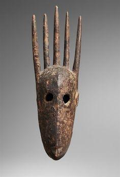 A BAMBARA MASK The face with pierced circular eyes, surmounted by five long projections, dark encrusted patina. 40 cm. high. Masque Theatre, Atelier D Art, Tribal Art, Headdress, Sculpture Art, Pet Stuff, African Sculptures, Contemporary African Art, Ceramic Mask