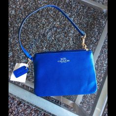 NWT COACH small wristlette, blue. New with tags condition.  Helpful note: I received this as an awesome gift but my iPhone 6 *in a case* does not fit in the purse.  The phone itself does fit, although tightly, without the case on.  Just didn't want you to purchase and be dissatisfied! Coach Bags Clutches & Wristlets