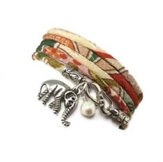 Next on my list: This wrap bracelet is made from traditional Japanese chirimen fabric made into a cord. Hanging from the S hook clasp is a lucky elephant and a genuine freshwater pearl. The fabric is a floral pattern with off-white, green, red, and a bit of orange. The bracelet is 35 inches long and will wrap around your wrist five times.