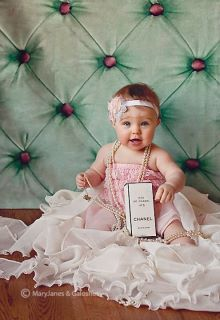 Cute baby girl wearing pearls & holding Chanel perfume!