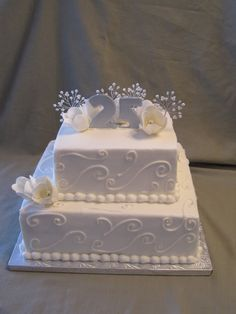 A 2-tier anniversary cake for a couple celebrating 25 years of marriage. Handmade sugar flowers and the gumpaste numbers. Scroll work is piped along the sides and silver beads are added as accents to help celebrate the silver anniversary.