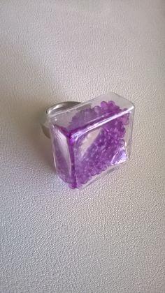 Bague avec cabochon carré 25 mm, rempli de micro billes mauve.