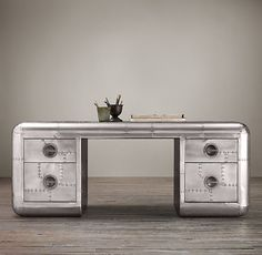 "77"" BLACKHAWK TRUNK DESK  $2495 SPECIAL $2120  Inspired by the gleaming nose cones and fuselages of mid-20th-century aircraft, this trunk is clad in a patchwork of polished aluminum panels accented with exposed steel screws. Rounded corners and inset drawer pulls give it sleek, aerodynamic lines."