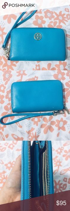 """Blue Tory Burch Wallet Beautiful blue Tory Burch wallet! It's such a lovely and bright color that's perfect for spring. Has a strap for easy carrying on your wrist (perfect for vacations when you only want to carry necessities), multiple slots to hold your cards and another little zip pouch inside to hold any extras. Some of the gold had flecked off on the logo but is hardly noticeable. Size: 6"""" L x 4"""" H Tory Burch Bags Wallets"""