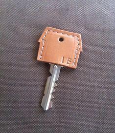 家の形のキーカバーです。エイジングの楽しめる牛ヌメ革を使用し、コバ処理(革の断面の処理)は素磨きでナチュラルに仕上げました。(別商品のペンケースと同じ革を使用しています。レザーキーカバー☆HOME #1より、薄めの色合いの革です。)「HOME」の刻印有り、無し、4文字以内での刻印変更をお選びいただけます。(写真のものは、刻印を変更した例になります)◆目安サイズ横幅35mm 縦幅28mm ご使用いただける鍵は 横幅26mmまでのものになります。◆材質牛革*1枚の革から複数個作っておりますので、写真のものと、表面の質感(皺、シボ感、ツヤなど)が若干異なることがございます。また、天然皮革なので、個体特有のキズや皺があることがございます。予めご了承ください。◆◆◆カスタマイズオプション◆◆◆刻印変更、刻印無しタイプへの変更、ステッチ色の変更を承ります。刻印に使用できる文字は、アルファベット(大文字)と数字のみです。カスタマイズオプションは、ご注文の際にお申し付けください。