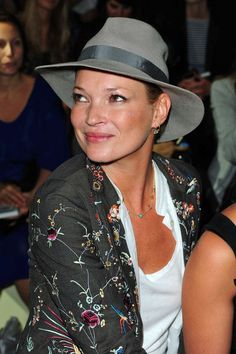 Kate Moss wearing a grey hat and embroidered jacket.