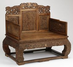 """Early 20th century Chinese huanghuali throne chair, ornately carved after an imperial example with allover decoration of dragons pursuing flaming pearls, the pierced crest surmounting the stepped back and arms, over a wide rectangular seat, all raised on elephant legs set into a base stretcher, 48""""h x 50""""w x 34""""d."""