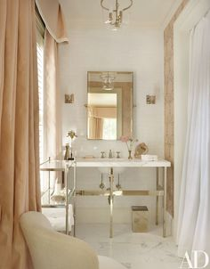 A guest bath features an étagère and mirror by Restoration Hardware and sconces from Circa Lighting; the washstand, sink fittings, and tiles are by Waterworks