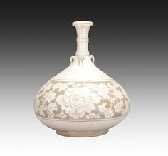 A CARVED CIZHOU VASE, Song Dynasty. The jar is pear-shaped. The exterior is decorated with lotus flowers connected by vines and leaves, the jar is also designed with multiple small handles. The jar has a pale white tone. 10 7/16 in. tall.
