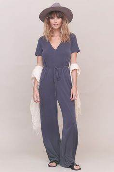 Knit wide leg jumpsuit. V-neckline. Tie waist with belt loops. Back keyhole with button closure. Unlined. Style #: 6R0063H Material: Modal/Polyester Color: Slate Model is wearing a small