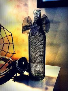 DIY: repurposed wine bottles with fishnet pantyhose, tulle, and bling.  And my favorite little crow has some bling too.