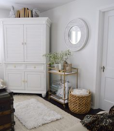 Spring Cottage Living Room at foxhollowcottage.com - Gold bar cart, White shuttered cabinet, white-washed round wood mirror.