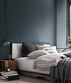 Dark grey lush bedding with deep rich accent colors- purple & indigo and wide variety of textures throughout the room... The wood and textiles.