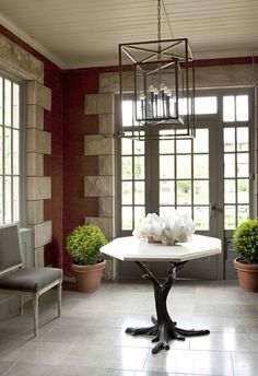 Nam Dang-Mitchell Interiors | House & Home : This brick- and sandstone-lined entry features formal furniture and simple shrubs, making it feel like an extension of the garden. A limestone-topped table and modern carriage lantern reflect the room's architectural gravitas.