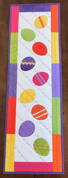 This charming runner will brighten your spring and Easter holiday. The colorful quilted runner features a variety of bright and cheerful fabrics. The runner has 9 appliqued eggs that are embellished with contrasting ric rac or decorative stitching. The background is quilted with a