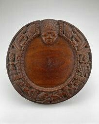 Opon Ifa: Mid-20th century Yoruba divination tray. Crafted by Areogun of Osi-llorin out of wood. The face of Education can be seen as well as kneeling mother's and cowry shells.