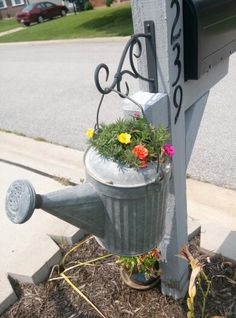Mailbox post with a watering can planter. Cute idea to hang something decorative on the back of the post!
