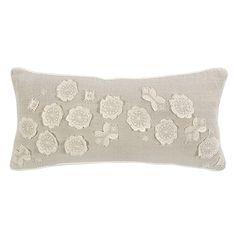 Thislong pillow decorates a bed or sofa with stunning sophistication. This plush Belgian linen accessory's delicate white floral lace appliques add a beautiful touch to its solid hue.