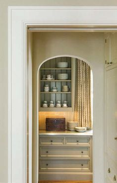 arch through to 'mini pantry' -  chunky white shelves, white rectangular tiles, curtain which can be drawn if desired but hidden otherwise. use to store stuff in jars, eggs, lemons, vegetables, etc.