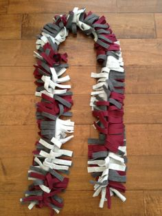 Fun scarf in 10 minutes. Would be cute for school spirit days in school colors. Lay strips, sew up enter line, cut fringe.
