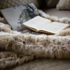 This faux fur blanket is the perfect gift for the homebody that loves to cozy up by the fire and read a good book - featured by Arhaus.