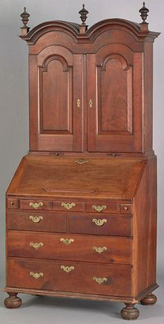 Pennsylvania William & Mary cherry secretary desk, circa 1735, the double bonnet top with interior, above a five drawer base with fully fitted interior and face carved prospect door.