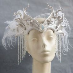 "Fabulously Evil!!!  Snowqueen Leather Crown  Sculpted headdress in pearl white, accented with a faux opal stone and braided satin trim. The sides flare into abstract twists and curls, trimmed with snow white ostrich feathers. Dripping with freshwater pearls and Swarovski crystals, which shower the wearer's face and neck with rainbows and glimmers. Measures approx. 12"" x 10"" at widest and tallest points. $225"