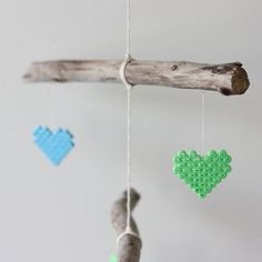 How to make a cute baby mobile from sticks of driftwood and Hama bead hearts.