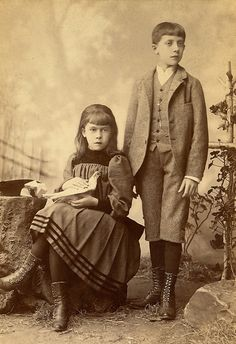 Young girl holding a bird while she poses with her brother, c. 1890s.