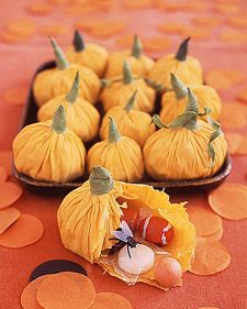 "Pumpkin Treat Holders* cut two 10"" circles from orange crepe paper. Stack circles & put candy in the center. Pull sides of paper up around treats to make a pouch. Gather paper just above the treats & twist a little. Secure by wrapping green floral tape around the base of the twist, binding upward to create pumpkin stem. If necessary, trim excess paper before binding. Foliage curls can be made by wrapping floral tape around a pencil."