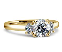 Two perfectly matched oval cut diamonds are prong set in this yellow gold diamond engagement ring setting, accenting your choice of center diamond.