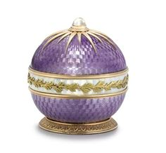 A RUSSIAN TWO-COLOUR GOLD-MOUNTED GUILLOCHÉ ENAMEL BELL-PUSH MARKED FABERGÉ AND WITH WORKMASTER'S MARK OF MICHAEL PERCHIN, ST. PETERSBURG, CIRCA 1890, AND WITH SCRATCHED INVENTORY NUMBER 59779 Spherical and with translucent mauve sides and a band of white enamel applied with a laurel branch and berry band, the moonstone push-piece set within a gold starburst motif, on a foliate slightly spreading foot. FROM THE COLLECTION OF KING GEORGE I OF THE HELLENES. Christie's.