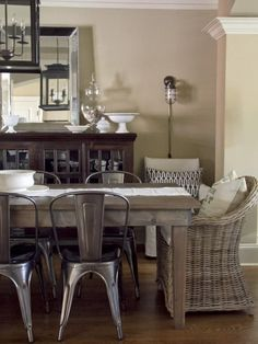 a mix of rustic metal chairs with wicker dining chairs pulled together with a rustic farmhouse table, buffet and lighting. rustic chic! want those wicker chairs in my home!