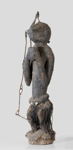 A Dogon fetish sculpture in shape of a monkey holding a cup in its hands, An iron-chain from th bottom to the head of the figure