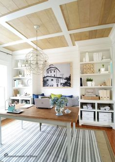 Accented with a rustic coffered ceiling, this gorgeous home office boasts a rustic wood bench placed beneath rope knot art and behind white cube accent tables