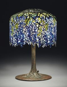 """Tiffany's circa 1910 """"Wisteria"""" leaded glass and bronze table lamp in deep purples, violets and blues. The lamp, which graced San Francisco's popular Eddie Rickenbacker bar, is being sold on June 14th by Christie's auction house in New York."""