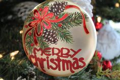 MERRY CHRISTMAS GLASS DISC ORNAMENT   The beauty of Christmas radiates with an elegantly designed glass Merry Christmas disc ornament. Enhanced with glittered pine greens, frosted pinecones, red bow with gem details will look amazing in a tree, bowl or wreath.  Merry Christmas!  SHOP www.exclusivelychristmas.com